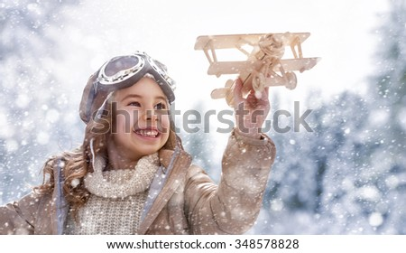 happy child playing with toy plane outdoors in winter - stock photo