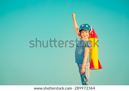 Happy child playing with toy rocket against summer sky background - stock photo