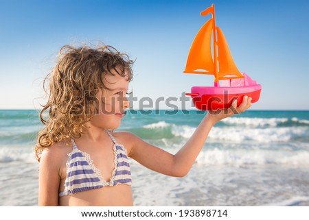 Happy child playing with toy sailing boat against blue sea and sky background. Smiling kid at the beach. Travel and adventure concept