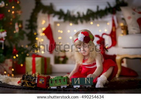 Happy child playing with toy train under christmas tree
