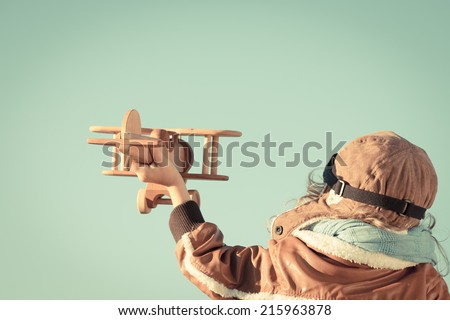 Happy child playing with toy wooden airplane against autumn sky background. Retro toned - stock photo