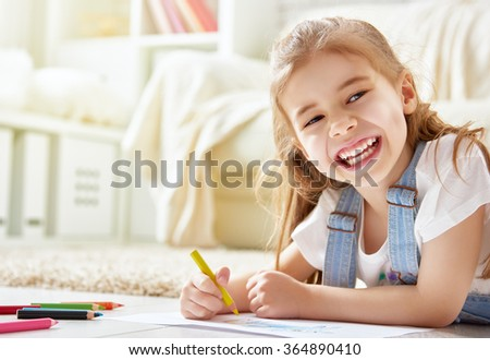 Happy child plays. Little child girl draws with colored pencils. - stock photo