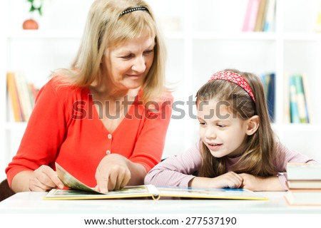 Happy child reading a book with help of her grandmother - stock photo