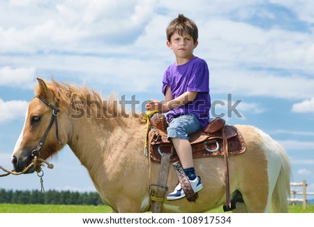 happy child ride farm animal brown pony with blue sky in background and beautiful nature