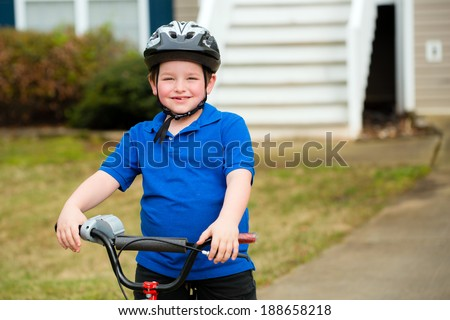 Happy child riding his bike outside his home - stock photo