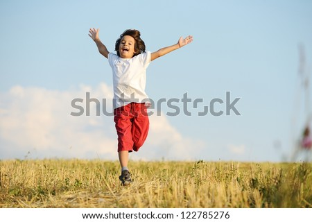 Happy child running on beautiful field