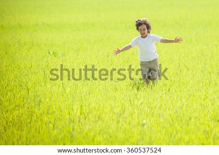Happy child running on beautiful green yellow grass field - stock photo