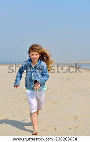 Happy child running on the beach for fashion concept - stock photo