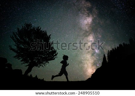Happy child running silhouette with Milky Way and beautiful night sky full of stars in background - stock photo