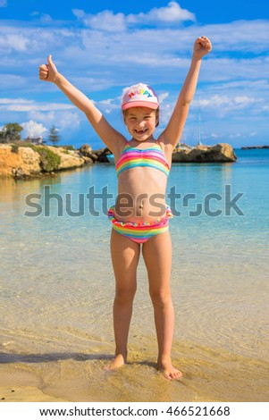 Happy child showing thumbs up on the beach. Summer holidays concept.