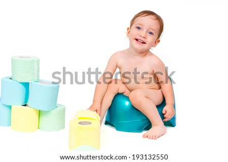 Happy child sitting on the potty and playing with toilet paper isolated on white background  - stock photo