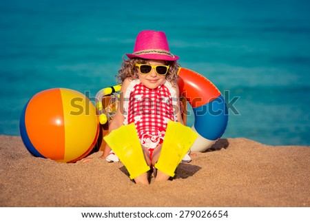 Happy child sitting on the sand. Funny kid on the beach. Summer vacation concept - stock photo
