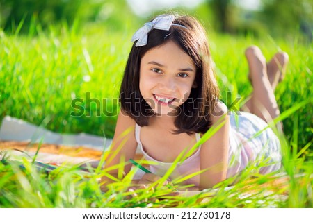 Happy child studying on nature with books - stock photo