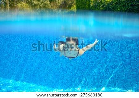 Happy child swims in pool underwater, active kid swimming, playing and having fun, children water sport  - stock photo