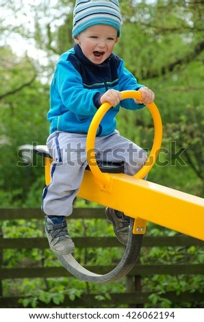 Happy child swinging on the playground in nature. Child concept. - stock photo