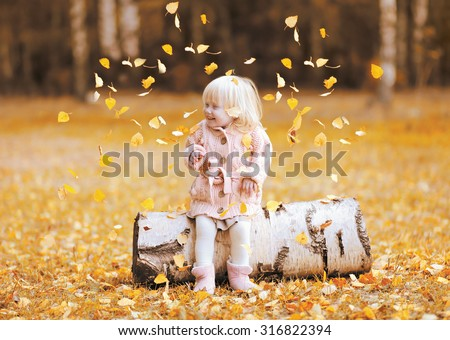 Happy child throws up yellow leaves and having fun in autumn park - stock photo