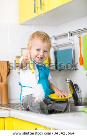 Happy child toddler boy washing the dishes in the kitchen - stock photo