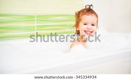 happy child toddler girl bathes in a bath with foam and bubbles - stock photo
