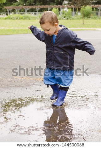 Happy child toddler playing in puddle after the rain. - stock photo
