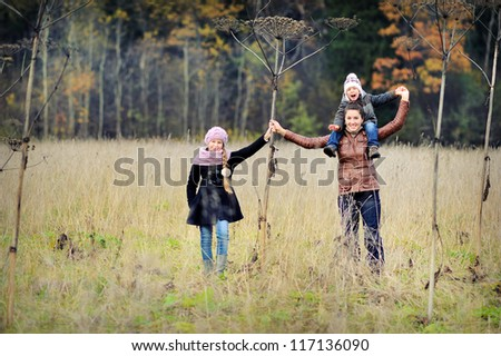 Happy child walking in autumn field. A boy plays with a long stick.