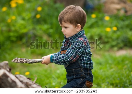 happy child walking in the garden, playing with a shovel. around direct dandelions