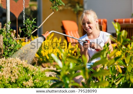 Happy child watering flowers in the garden in front of her family home
