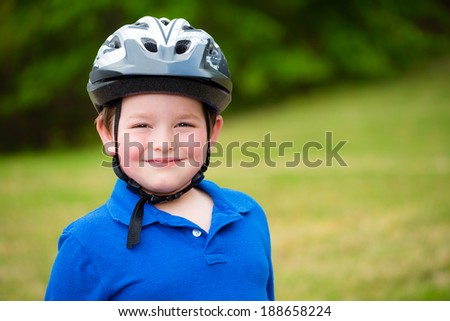 Happy child wearing a bike helmet outdoors - stock photo