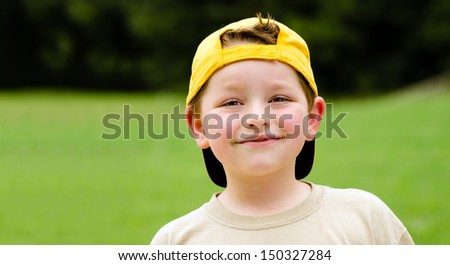 Happy child wearing yellow ball cap in outdoor portrait - stock photo