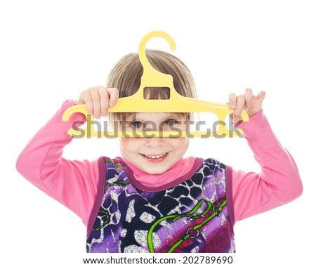 Happy child with a coat hanger in his hand on a white background.