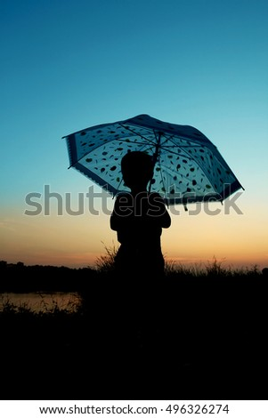 happy child with an umbrella silhouette on nature in the park sunset