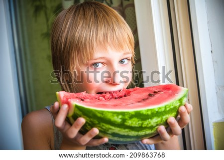 Happy child with big red slice of watermelon