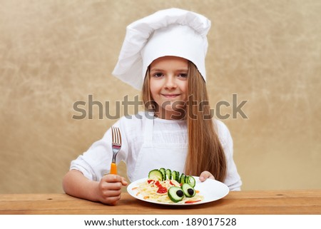 Happy child with chef hat holding pasta dish with cucumber creature decoration - stock photo
