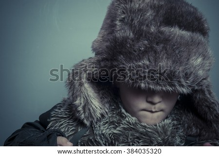 Happy  child with fur hat and winter coat, cold concept and storm