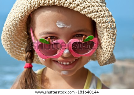 Happy child with glasses on nose with sunscreen on my face - stock photo