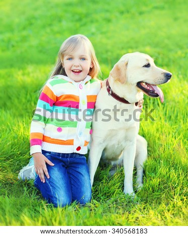 Happy child with labrador retriever dog on grass in summer