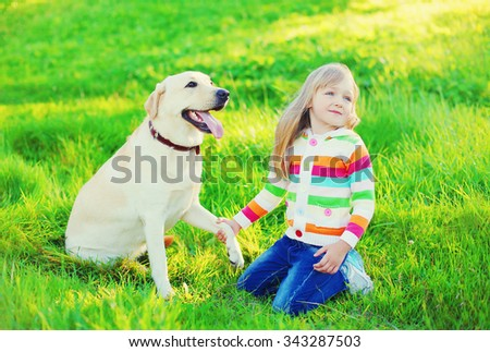 Happy child with labrador retriever dog on grass in summer day