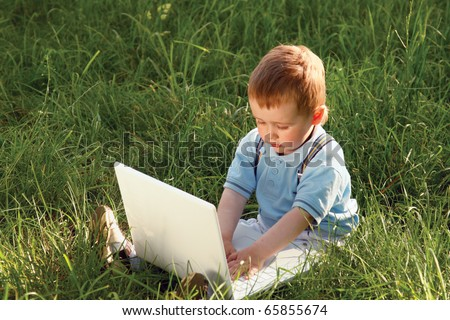 happy child with laptop in nature - stock photo