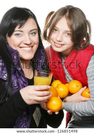 happy child with mother holding oranges and juice