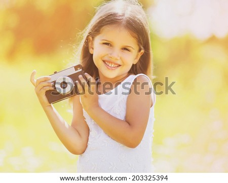 Happy child with old retro vintage camera having fun outdoors in sunny day - stock photo