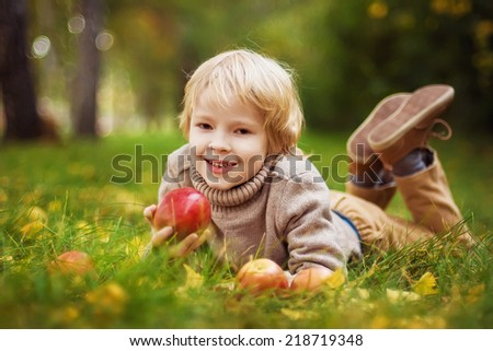 Happy child with red apples in autumn park - stock photo