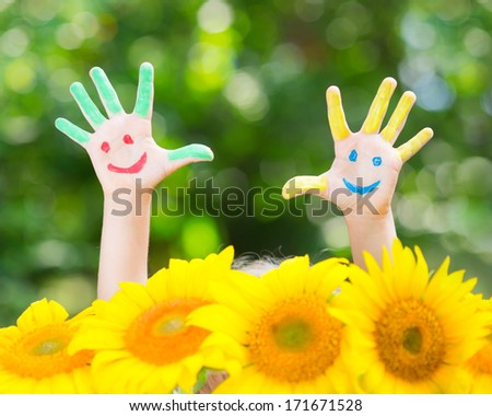 Happy child with smile on hands against green spring background - stock photo