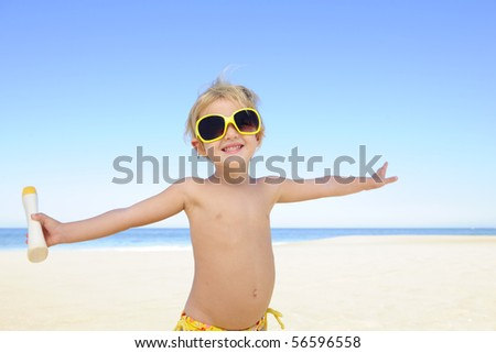 happy child with sunglasses and suntan lotion at the beach