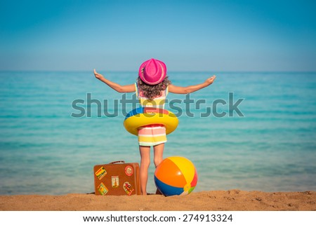 Happy child with vintage suitcase on the beach. Summer vacation and travel concept - stock photo