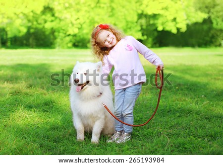 Happy child with white Samoyed dog on the grass in sunny summer day - stock photo