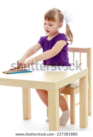 Happy childhood, adolescence, the development of the family concept.Little girl draws pencils sitting at the table. Isolated on white background. - stock photo