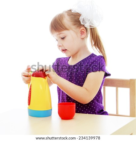 Happy childhood, adolescence, the development of the family concept.Little girl sitting at the table pouring from a plastic tea kettle. Isolated on white background.