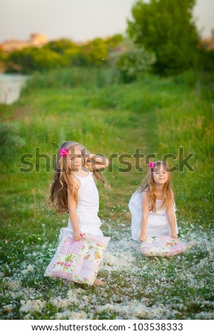 Happy childhood: Adorable little girls having fun with pillows outdoor