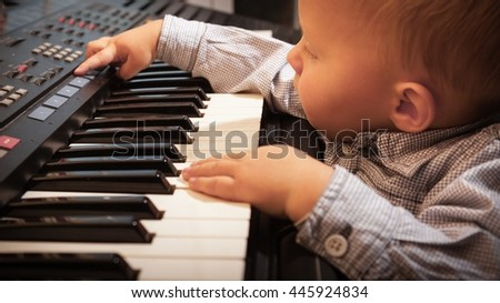 Happy childhood and music. Little boy child kid playing on the black digital midi keyboard piano synthesizer musical instrument indoor. - stock photo