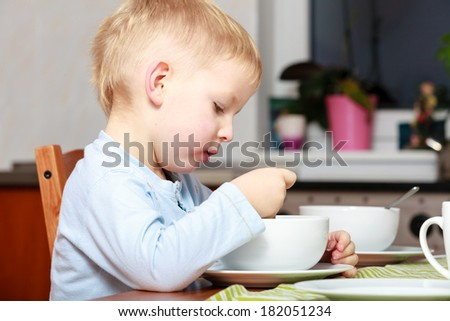 Happy childhood. Blond boy kid child eating corn flakes cereal with milk breakfast morning meal at the table. Home. - stock photo