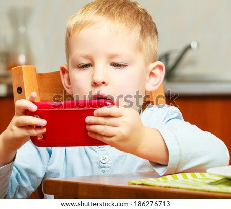 Happy childhood. Blond boy kid child playing with mobile phone at the table. Home.